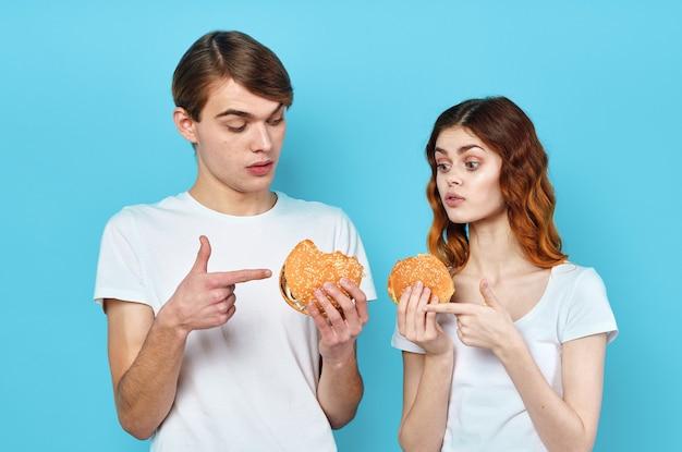 Homme et femme en t-shirts avec des hamburgers entre les mains du régime de restauration rapide