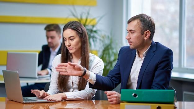 Homme et femme à la table de réunion