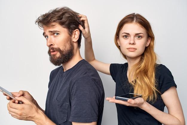 Homme et femme avec un téléphone à la main émotions studio lifestyle. photo de haute qualité