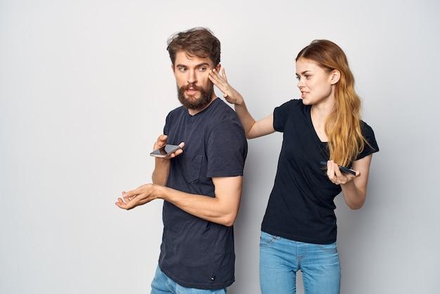 Homme et femme avec un téléphone à la main émotions studio lifestyle