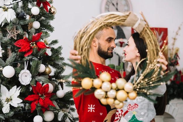 Homme et femme tenant une guirlande de noël