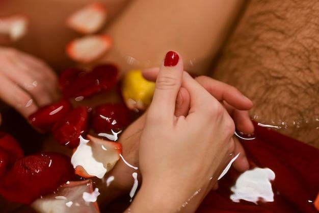 Homme, femme, tenant mains, dans, les, gros plan baignoire