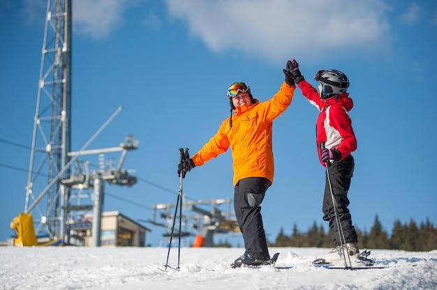Homme, femme, tenant mains, à, skis, sur, sommet montagne