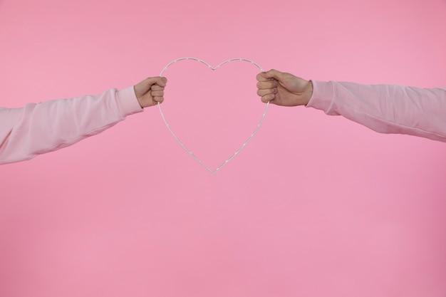 Homme et femme tenant un symbole décoratif du coeur