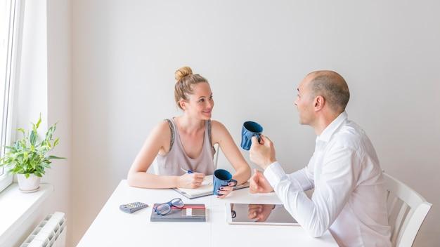 Homme et femme tenant une tasse à café en céramique bleue discutant au lieu de travail