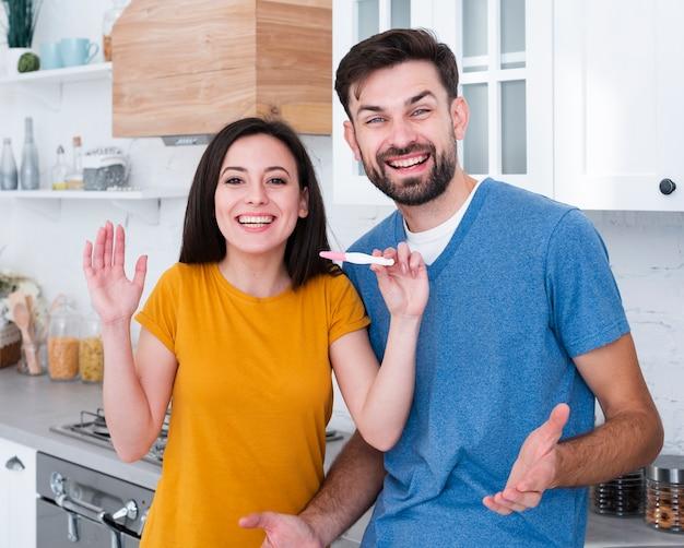 Homme et femme tenant un test de grossesse