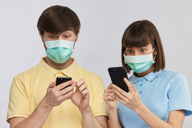 Un homme et une femme terrifiés à la recherche de téléphones portant des masques antipandémiques protecteurs, covid-19 news