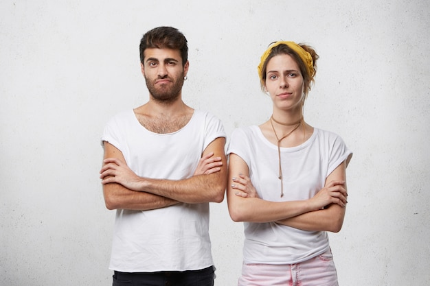 Homme et femme têtus en colère debout dans des postures fermées, gardant les bras croisés, face à un désaccord dans les relations tout en ayant un conflit ou une querelle
