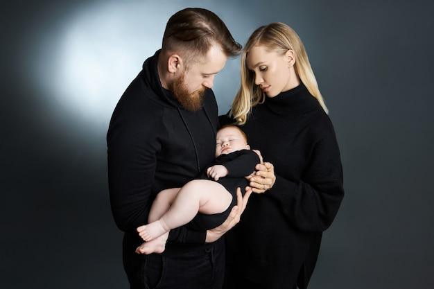 Un homme et une femme tiennent un bébé dans leurs bras. portrait d'un couple marié après la naissance d'un enfant. jeune famille
