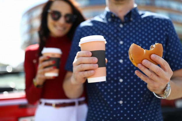 Homme et femme tiennent le café et le hamburger