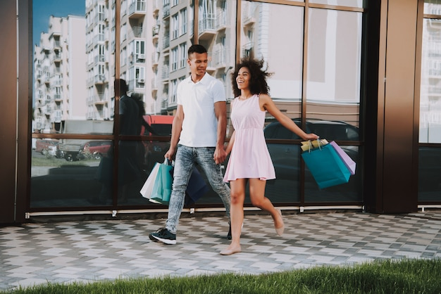 Homme et femme tient des sacs de shopping sunshine summer day