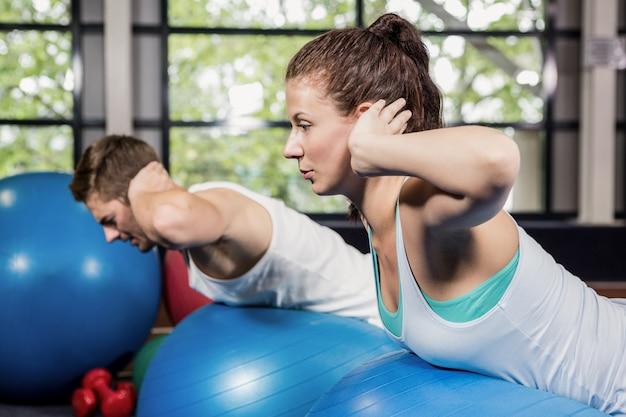 Homme et femme travaillant sur ballon de fitness