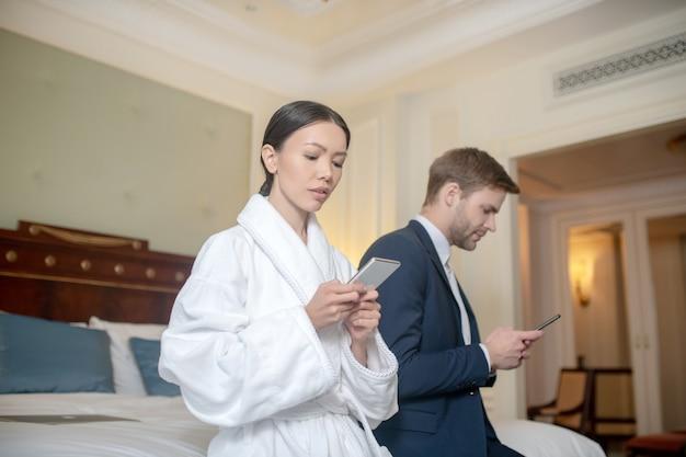Un homme et une femme utilisant leurs smartphones dans la chambre