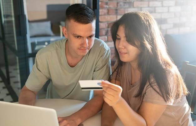 Homme et femme utilisant un ordinateur portable pour faire des achats en ligne avec une carte de crédit