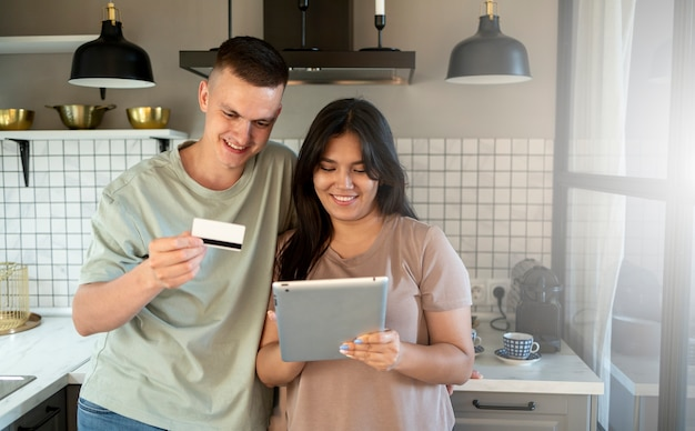 Homme et femme utilisant une tablette pour faire des achats en ligne avec une carte de crédit