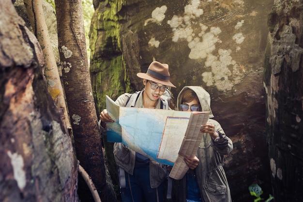 L'homme et la femme utilisent la carte pour voir les sentiers de randonnée.