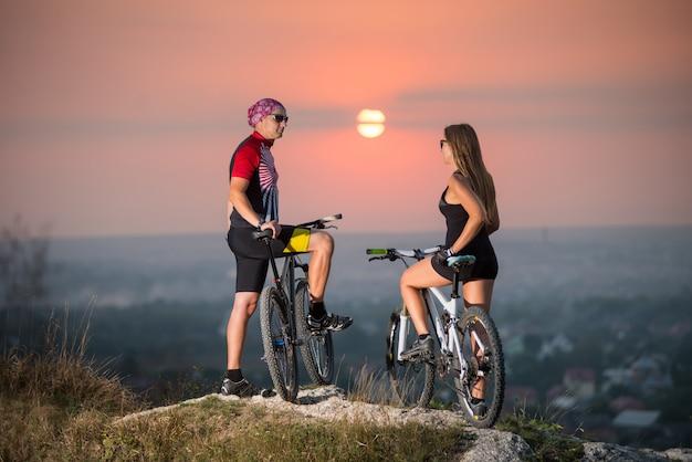 Homme et femme sur un vélo de montagne, debout sur les rochers de la falaise, se retournant vers la caméra.