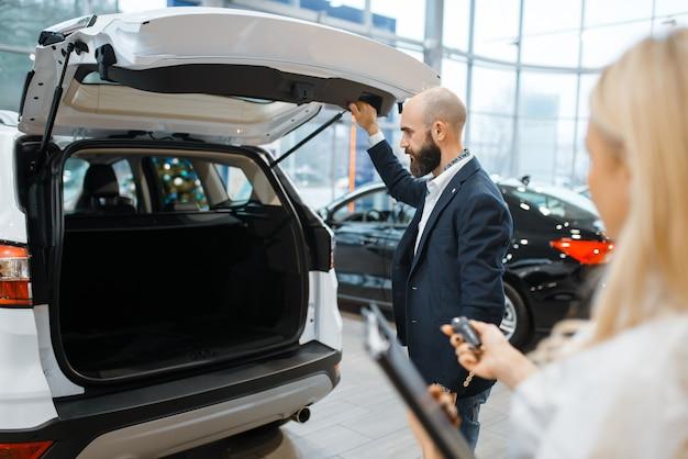 Homme et femme vendeur à la recherche d'une voiture chez le concessionnaire automobile.