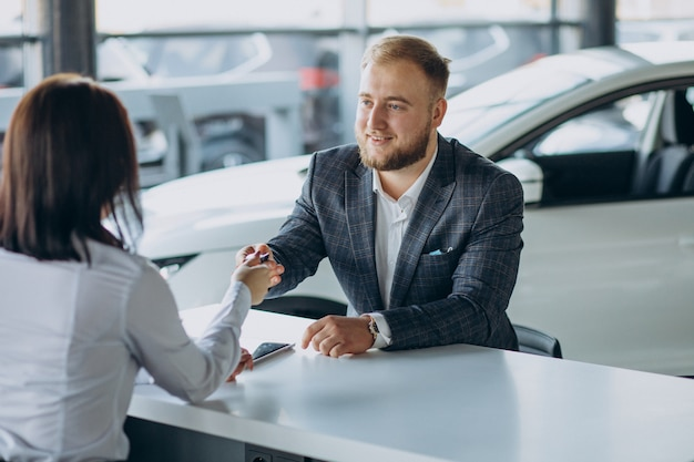 Homme avec femme de vente dans la salle d'exposition de voiture