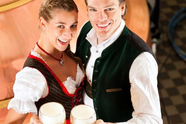 Homme et femme avec verre à bière dans une brasserie