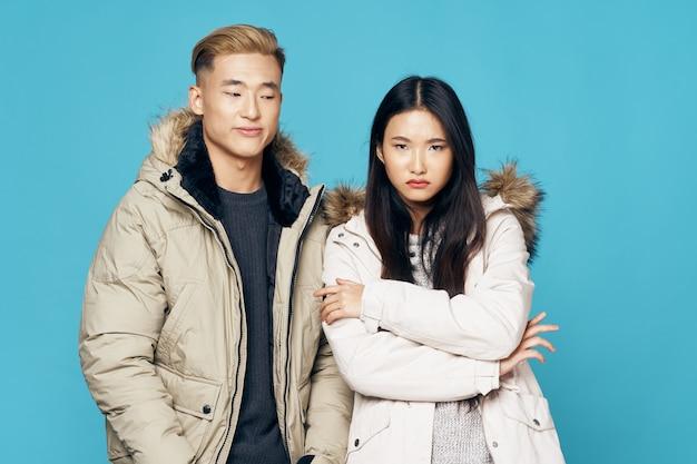 Homme et femme en vestes d'hiver aspect asiatique mode style de vie fraîcheur fond bleu