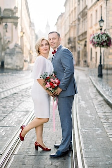 Homme et femme en vêtements de luxe, posant ensemble sur le chemin de fer du tramway dans l'ancien centre-ville