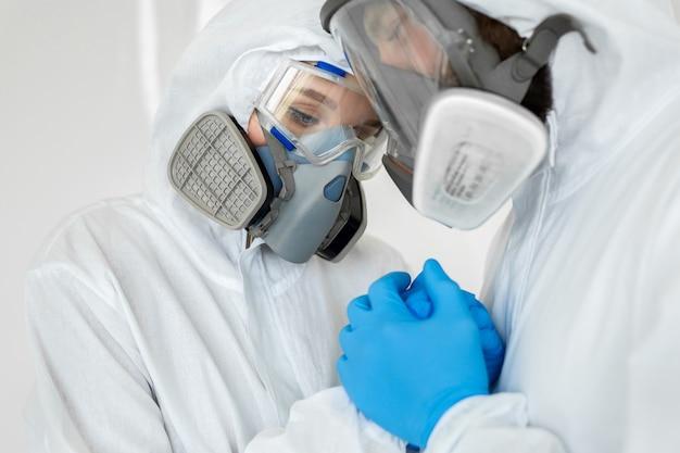 Un homme et une femme vêtus de combinaisons de protection et de respirateurs, se tenant la tête pendant la quarantaine