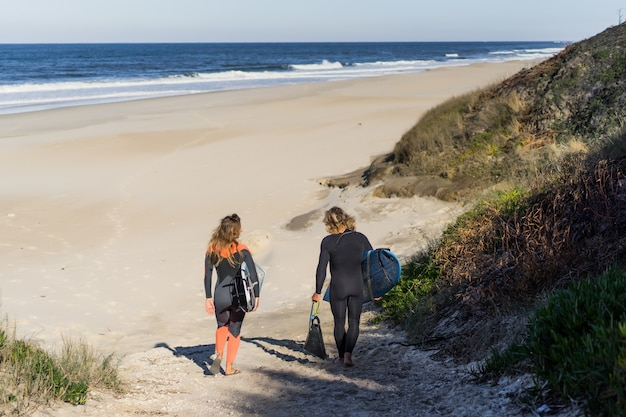 Homme et femme vont à l'océan avec des planches de surf. homme et fille vont surfer