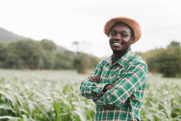 Homme de fermier africain se tenir à la ferme verte avec heureux et sourire.
