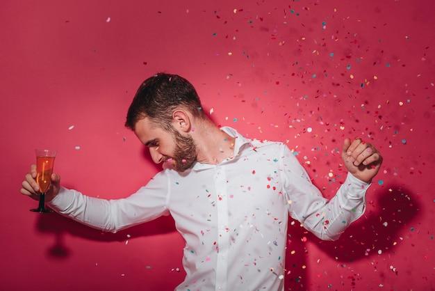 Homme de fête posant avec des confettis