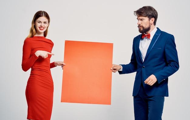 Un homme avec une feuille de papier rouge dans ses mains et une femme dans une robe affiche publicitaire mocap