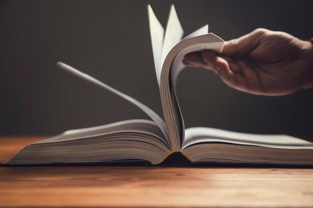 Un homme feuillette les pages d'un livre sur une surface sombre