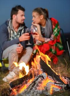 Un homme et une fille boivent du vin sous un feu de joie romantique.