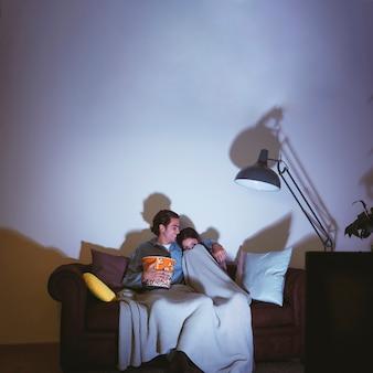 Homme et fille effrayée ayant une soirée de cinéma