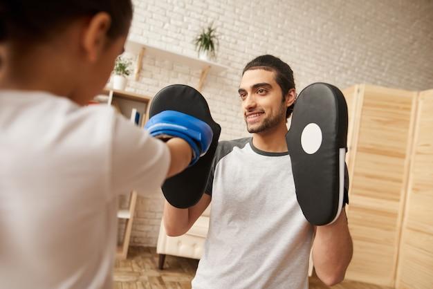 Homme et fille ont une formation de boxe à la maison.