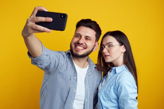 Homme et fille prenant selfie en studio isolé sur mur jaune