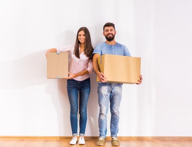 Un homme et une fille se tiennent avec des boîtes.