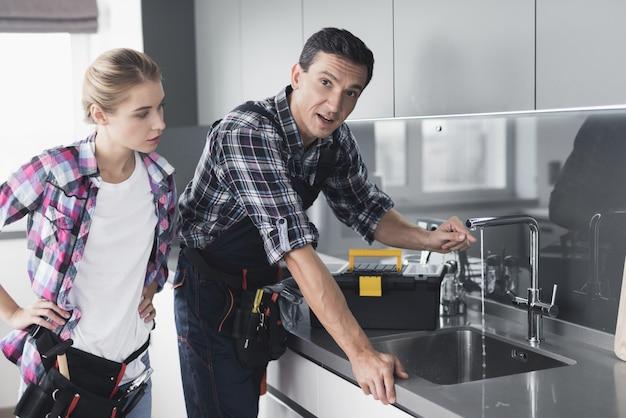 Un homme et une fille vérifient que l'évier n'est pas cassé.