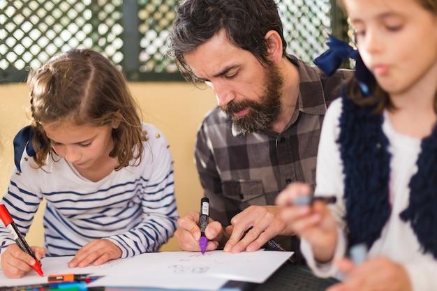 Homme avec des filles dessiner des images