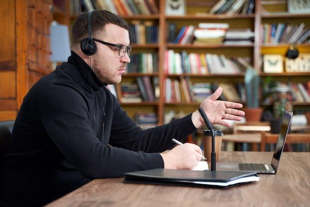 Homme filmant le blog vidéo sur la caméra avec un trépied pour les adeptes en ligne. dans les médias sociaux, influencer, nouvelles technologies, communication et concept internet