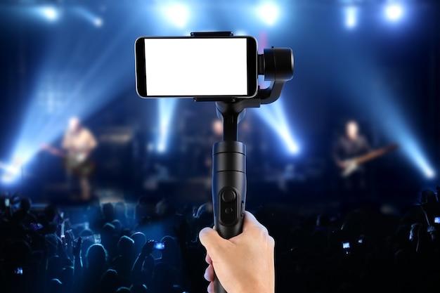 Homme Filmant Avec Un Smartphone à écran Vide à L'aide D'un Stabilisateur De Cardan, Isolé Sur Un Spectacle De Musique. Mise Au Point Sélective. Photo Premium