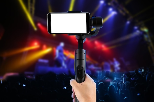 Homme filmant avec un smartphone à écran vide à l'aide d'un stabilisateur de cardan, isolé sur un spectacle de musique. mise au point sélective.