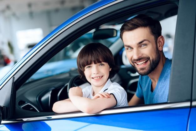 Homme avec fils sont assis au volant d'une voiture neuve.