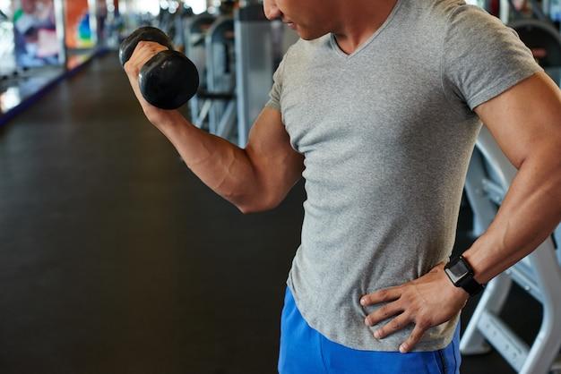Homme fit méconnaissable faisant biceps curl avec haltères en gym