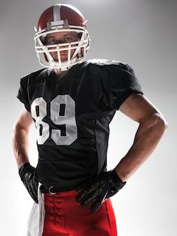Homme de fitness caucasien en tant que joueur de football américain sur blanc