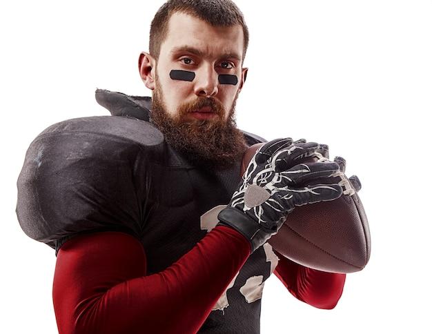 Homme de fitness caucasien en tant que joueur de football américain tenant un ballon sur blanc