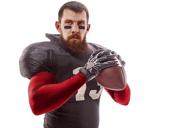 Homme de fitness caucasien en tant que joueur de football américain tenant un ballon sur fond blanc