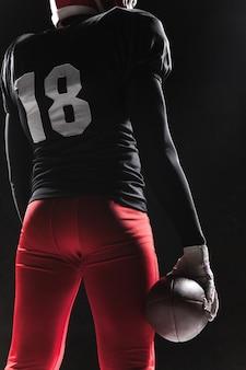 Homme de fitness caucasien en tant que joueur de football américain tenant un ballon sur fond noir