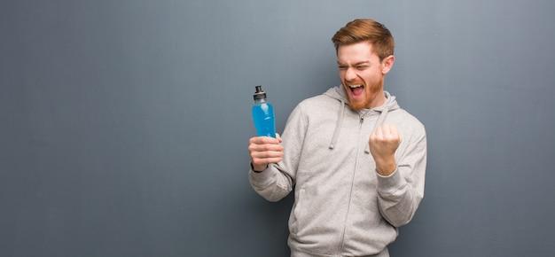 Homme de fitness jeune rousse surpris et choqué. il tient une boisson énergisante.