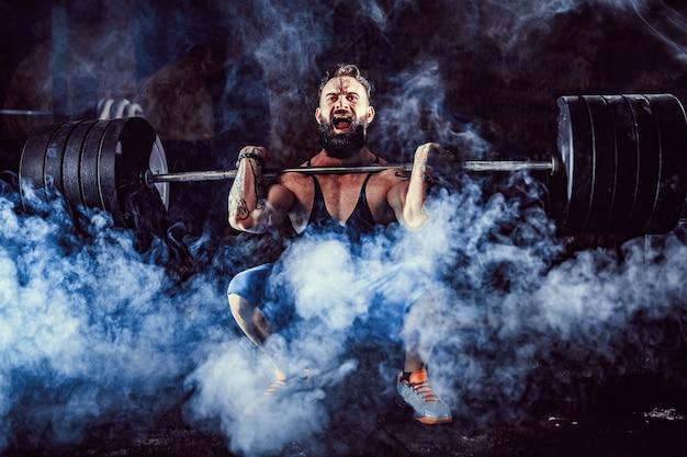 Homme de fitness musclé faisant deadlift une barre de poids sur sa tête dans un centre de fitness moderne. entraînement fonctionnel.
